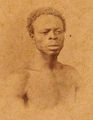 Photograph taken from Christiano Junior. The subject's name, place of birth and time of arrival to Brazil was not recorded. However, the scarifications suggest Oyo affiliation, and it is conceivable this individual arrived to Brazil as a child in the late-1820s and early 1830s, suggesting he was involved in Oyo's collapse.   See http://brasilianafotografica.bn.br/brasiliana/handle/20.500.12156.1/6503