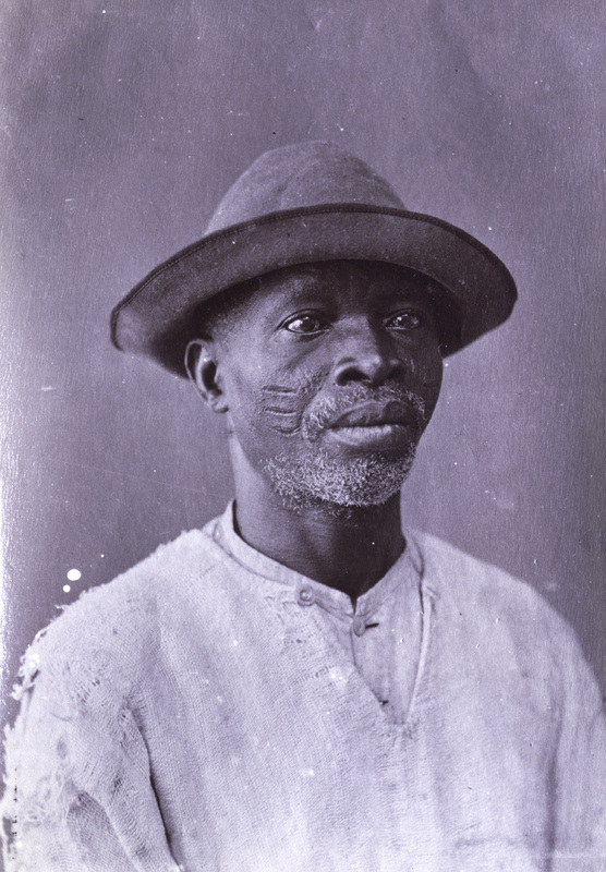 """The subject's name, place of birth and time of arrival to Brazil was not recorded. However, the scarifications suggest Oyo affiliation, and it is conceivable this individual arrived to Brazil likely as a child after the final abandonment of the of capital district in Oyo in 1836. More research is being conducted to known about this subject and the photograph which was taken 1910. Given the lateness of this image, this individual was likely born and enslaved after the final abandonment of the capital city of Oyo in 1836. The scars are are still indicative of Oyo affiliation and this individual had to have arrived before the last ship arriving from the Bight of Benin in 1851.   See Schomburg Center for Research in Black Culture, Jean Blackwell Hutson Research and Reference Division, The New York Public Library. """"A Bahian Negro; Probably from Lagos, West Africa."""" The New York Public Library Digital Collections. 1910. http://digitalcollections.nypl.org/items/510d47db-b752-a3d9-e040-e00a18064a99"""